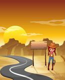 A cowgirl standing beside an empty wooden signboard along the ro Stock Images