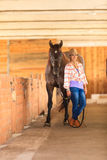 Cowgirl standing next to brown horse friend. Taking care of animals, love and friendship concept. Cowgirl in checkered shirt and cowboy hat leading brown horse stock photos