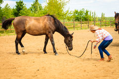 Cowgirl standing next to brown horse friend. Taking care of animals, love and friendship concept. Cowgirl in checkered shirt and cowboy hat leading brown horse royalty free stock photos