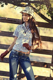 Cowgirl in stetson next to wooden fence Stock Image