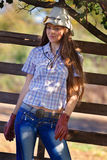 Cowgirl in stetson next to wooden fence stock photo