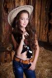 cowgirl style model posing on farmland near hay stock photo
