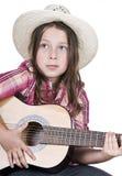 Cowgirl sveglio che gioca la sua chitarra Fotografia Stock