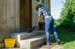 Cowgirl sweep stairs with wooden broom in rural Stock Images