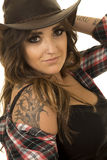 Cowgirl with tattoos sit close hat small smile. A cowgirl up close with her tattoo on her shoulder showing royalty free stock image