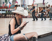 Cowgirl texting at Rocking the Park event in Milan, Italy Royalty Free Stock Photos
