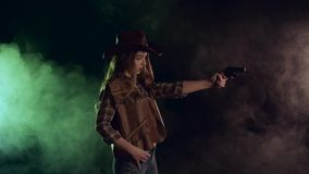 Cowgirl trzyma kolt w ona ręki i celowanie przy czarnym charakterem Czarny dymny tło swobodny ruch Boczny widok zbiory