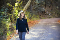 A Cowgirl Walks a Forest Road in the Fall Royalty Free Stock Photo
