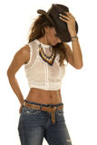Cowgirl in white top with hat hand on it Royalty Free Stock Photos