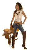 Cowgirl in a white top holding a saddle looking to the side Royalty Free Stock Image