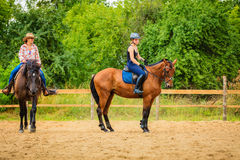 Cowgirl and woman jockey riding on horses Royalty Free Stock Images
