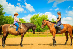 Cowgirl and woman jockey riding on horses Stock Photo
