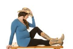 Cowgirl z kapeluszem ciężarnym siedzi pełnego ciało Zdjęcia Stock