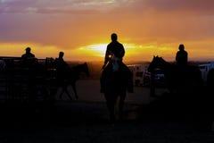 Cowgirlkonturer framme av en färgrik solnedgång Arkivbilder