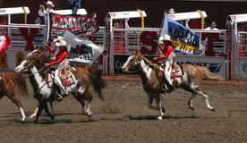 Cowgirls galloping on horseback Stock Photography