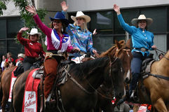 Cowgirls riding horses in parade Stock Photography