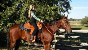 Cowgirlsammanträde på en häst Arkivbilder
