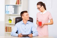 Coworker brings a cup of drink to her partner. Couple at work.  Female coworker holding a cup of coffee for her office boyfriend Stock Photography