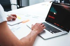 Coworker mężczyzna używa laptop i drukowanego projekt w nowożytnym biurze fotografia stock