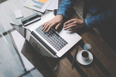 Coworker man working with laptop at office.Modern notebook, cup of black coffee and smartphone on the wooden table. Horizontal, blurred Royalty Free Stock Image