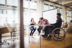 Coworker na wózku inwalidzkim z fotografia redaktorami w pokoju konferencyjnym Fotografia Stock