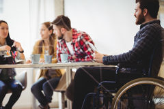 Coworker on wheelchair using digital tablet against photo editors Royalty Free Stock Image