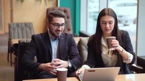 Coworkeren kommer med ett kaffe till flickan, och de startar att diskutera projektet med en bärbar dator i kafé stock video