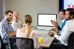 Coworkers applauding a colleague during a video conference. In the conference room Stock Image