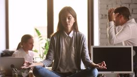 While coworkers arguing woman sitting at desk focused on meditation
