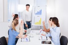 Coworkers asking queries to team leader. Business Coworkers Raising Hand For Asking Queries To Team Leader Royalty Free Stock Images