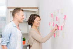 Coworkers are attaching post-it notes to the wall Royalty Free Stock Photography