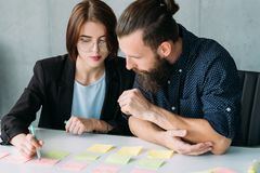 Coworkers brainstorming marketing strategy notes stock image
