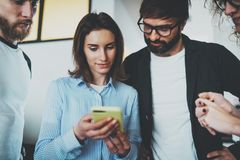 Coworkers business meeting concept.Young team using mobile device at modern office. royalty free stock image