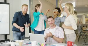 Coworkers celebrating victory in office. Group of multiethnic people in casual clothing standing at table with laptop and celebrating winning giving high five stock video footage