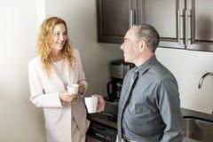 Coworkers on coffee break. Business colleagues having conversation in office coffee break area royalty free stock photo