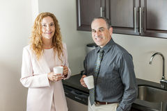 Coworkers on coffee break. Two office coworkers on coffee break standing in kitchen stock images
