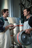 Coworkers discussing while examining kegs. At warehouse Stock Photography