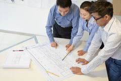 Coworkers discussing project in the office, looking down Stock Photography