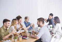 Coworkers eating lunch together. Multicultural team of coworkers eating a healthy lunch together at the office Royalty Free Stock Images