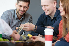 Coworkers enjoying their meal. Cheerful coworkers enjoying their healthy, oriental meal Stock Photography