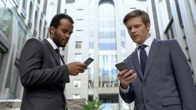 Coworkers exchanging contacts on smartphones profitable acquaintance, social app. Stock photo stock photos