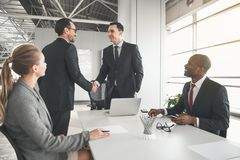 Coworkers getting together in conference hall stock images