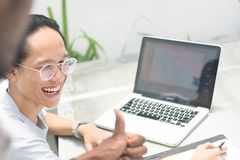 A coworkers give thumb up at friend, young asian man with glasses with laptop and notebook get thumb up from friend royalty free stock photo