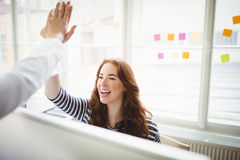 Coworkers giving high-five in creative office Stock Photos