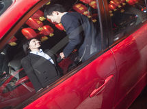 Coworkers handshaking next to the car at night, red lanterns on the background Stock Image