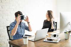 Coworkers having fun with VR glasses Stock Photo