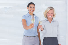 Coworkers holding flutes of champagne Stock Images