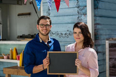 Coworkers holding writing slate while standing by food truck Royalty Free Stock Photo