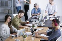 Coworkers i modernt kontor fotografering för bildbyråer