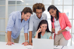 Coworkers interacting with laptop computer Stock Photos